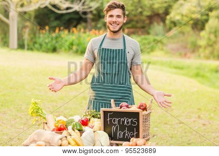 Handsome farmer standing at his stall on a sunny day