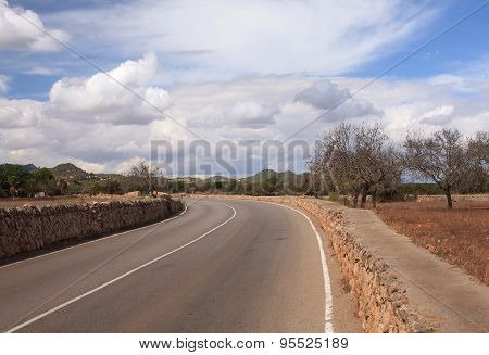 Bending road with markings among the stone walls and trees