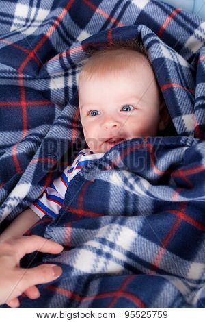 Cute baby boy hiding beside plaid