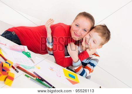 Happy son and mother hugging each other at desk