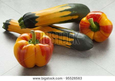 Fresh raw striped yellow and red peppers and green yellow striped zucchini