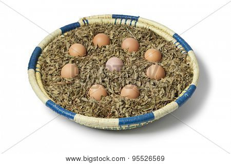 Eggs in a basket with dried henna leaves as a symbol for a Moroccan wedding party on white background