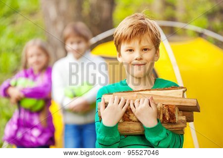 Portrait of boy holding the wood for bonfire