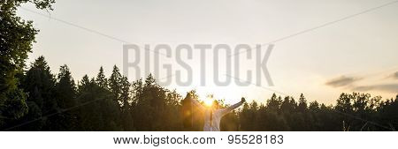 Businessman In A Woodland With His Arms Outspread Celebrating Success