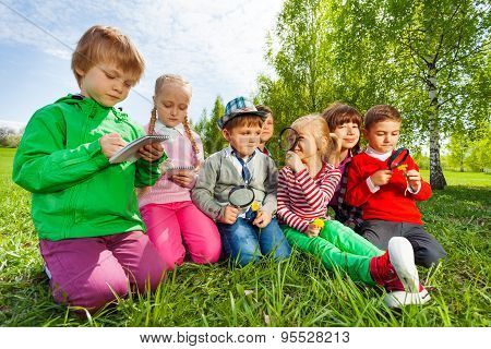 Group of kids sit in the field with magnifier