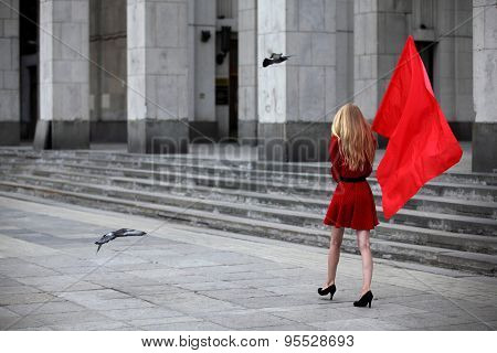 A blonde woman with a red flag