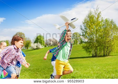 Happy running kids with white airplane toy