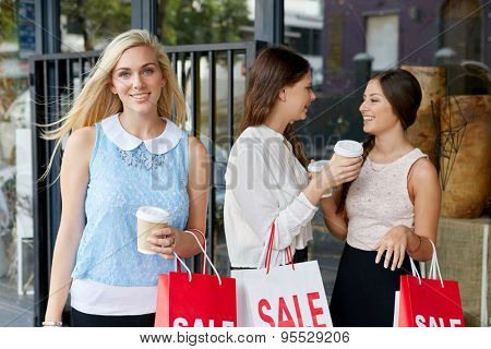 portrait of beautiful teen girl shopping in city with friends standing outdoors