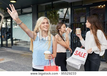 young happy girl calling for taxi cab along city sidewalk with coffee cup sale shopping bag friends