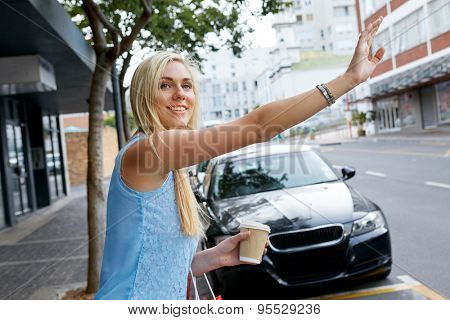 young happy girl calling for taxi cab along city sidewalk with coffee cup