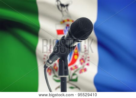 Microphone On Stand With Canadian Province Flag On Background - Yukon