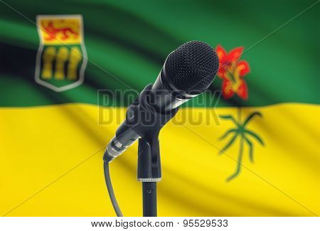Microphone On Stand With Canadian Province Flag On Background - Saskatchewan