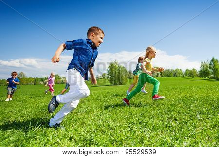 Happy running kids in the green park during day