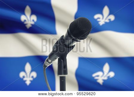 Microphone On Stand With Canadian Province Flag On Background - Quebec