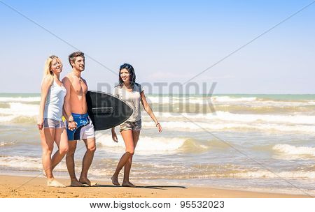 Group Of Young Happy People On Vacations At The Beach Holding A Surf Table - Best Friends