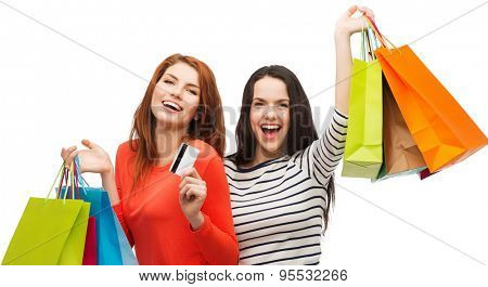 shopping, sale and gifts concept - two smiling teenage girls with shopping bags and credit card