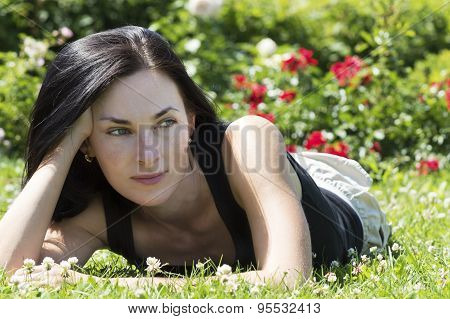 Woman Lying In Grass Wih Flowers In Background