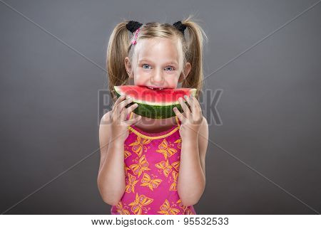 Little toothless girl eating watermelon.