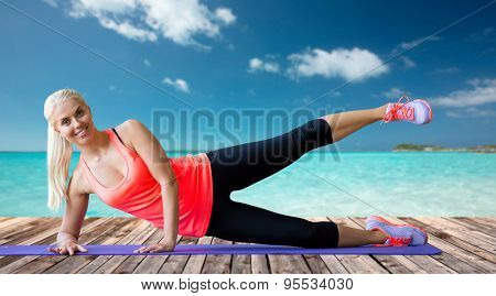 fitness, sport, exercising and people concept - smiling woman raising leg on mat over sea and wooden berth at resort background