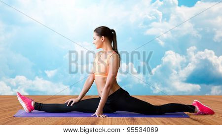 fitness, sport, exercising, stretching and people concept - smiling woman doing splits on mat over wooden floor and sky with white clouds background