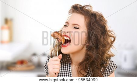 people, diet, culinary and food concept - hungry young woman eating meat on fork over kitchen background