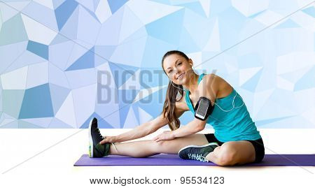 fitness, sport, training, technology and people concept - smiling woman with smartphone and earphones listening to music and stretching leg on exercise mat over blue low poly background