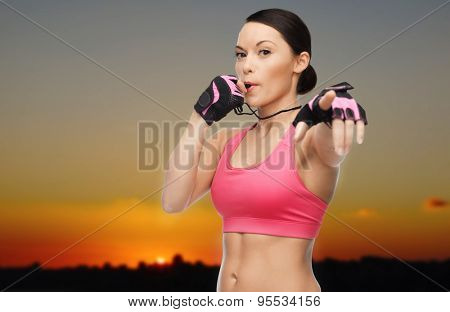 people, sport, fitness and healthy lifestyle concept - happy asian woman coach blowing whistle outdoors over sunset skyline background