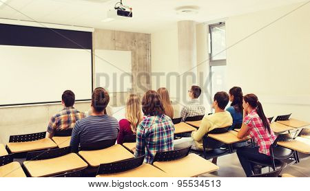 education, high school, teamwork and people concept - group of students sitting in lecture hall from back
