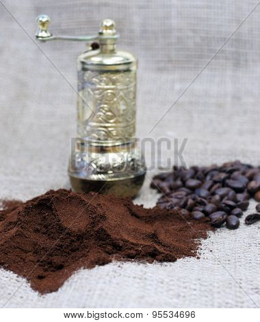 Old coffee grinder with coffee beans and powder