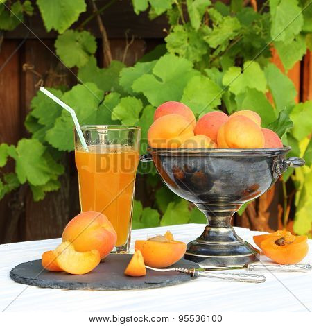 Apricots In A Metal Vase And A Glass Of Apricot Juice
