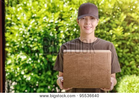 Attractive Delivery Woman With A Cardboard Box