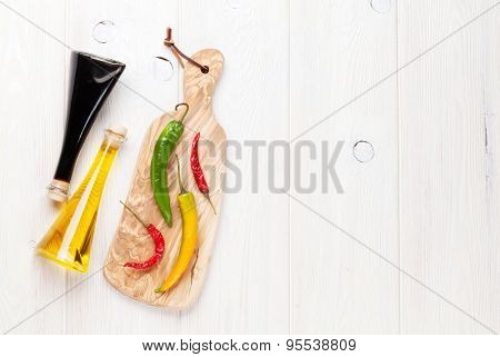 Colorful chili peppers and condiments on white wooden table. Top view with copy space