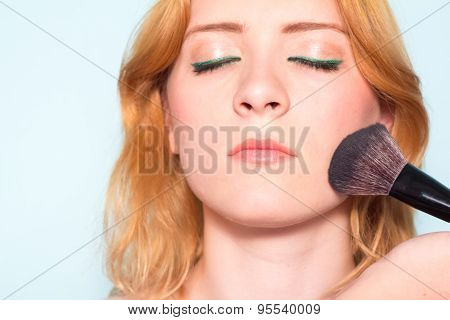 Makeup artist paints a woman blush cheekbones. Makeup.
