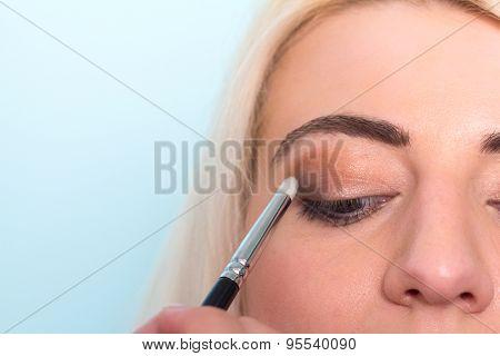 Makeup artist paints a eyes of woman. Makeup.