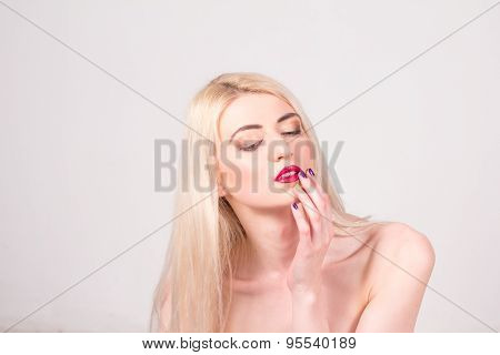 Beauty concept. Beautiful woman with blond straight hair and red lips touching her lips. Manicure