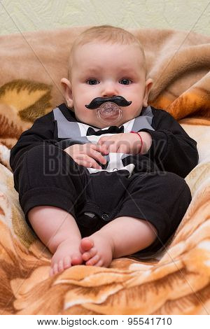 Toddler with pacifier is lying on plaid mustache