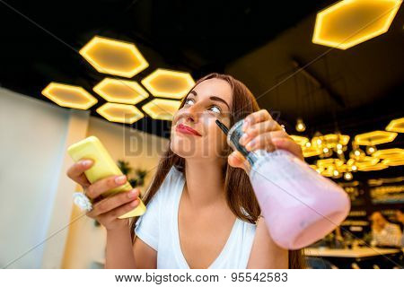 Woman with phone and drink in modern interior