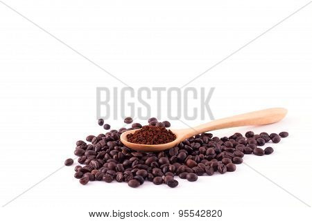 Coffee beans and ground coffee on wooden spoon isolated on white background.
