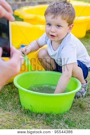 Cute Baby Boy Is Playing With Water And Posing