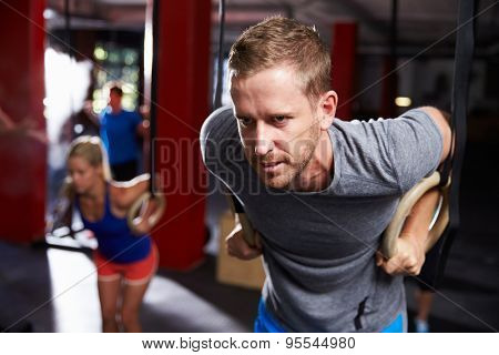 Man In Gym Exercising With Gymnastic Rings
