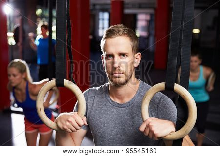 Portrait Of Man In Gym Exercising With Gymnastic Rings