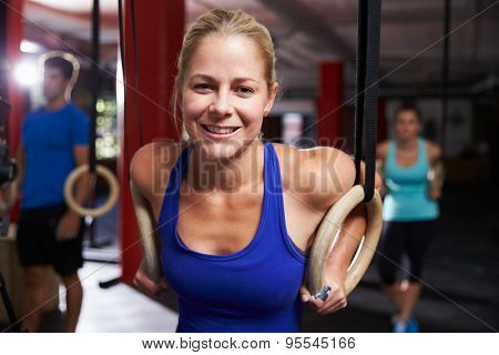 Portrait Of Woman In Gym Exercising With Gymnastic Rings