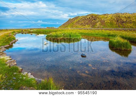 Small lake with thermal water. In the smooth surface of the water reflects the sky and clouds