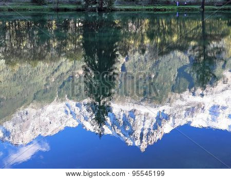 Chamonix - a famous ski resort in the French Alps. Reflections of snow-capped peaks and coastal trees in city park pond