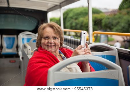 Senior woman with phone on a tour bus, Saint-Petersburg, Russia