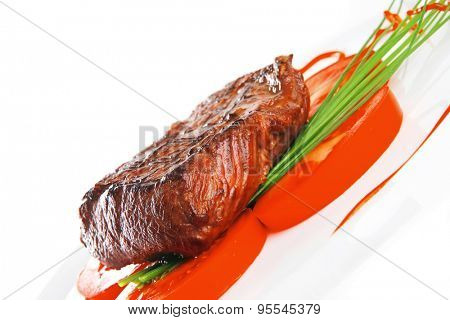 grilled beef meat entrecote fillet served with tomatoes and green chives  on white china plate isolated over white background