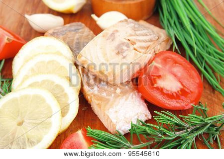 savory sea fish entree : roasted salmon fillet with green onion, red cherry tomatoes pieces,  rosemary twigs and lemon on wooden board isolated on white background
