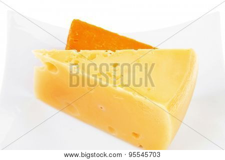 dairy product : two pieces of french gourmet cheeses (parmesan and cheddar) on plate isolated over white background