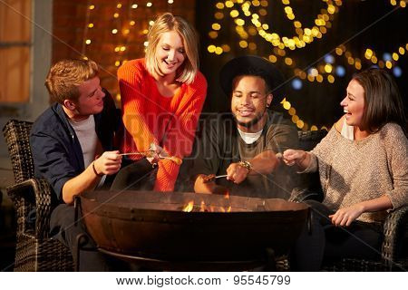 Group Of Friends Cooking Sausages By Firepit