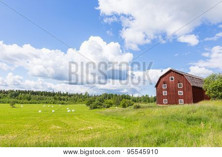 Scenic View Of An Old Barn With White Silage